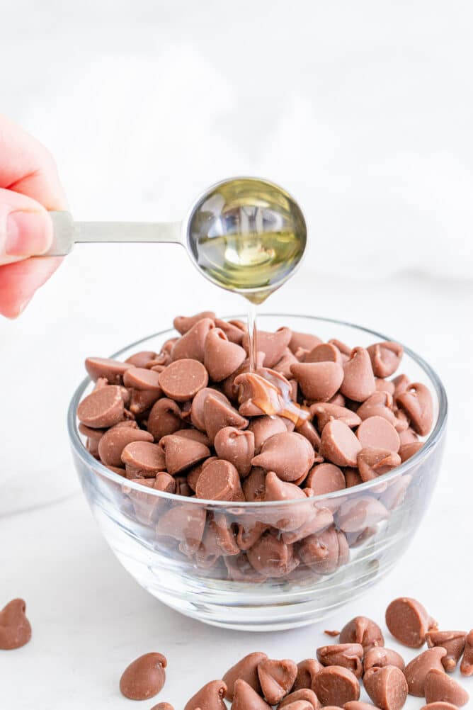 Teaspoon of oil being poured into a bowl of milk chocolate chips