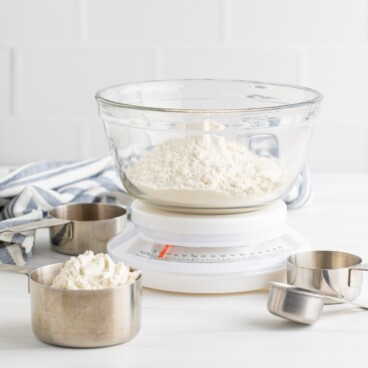 Flour in a glass mixing bowl on top of a kitchen scale with measuring cups off to the side