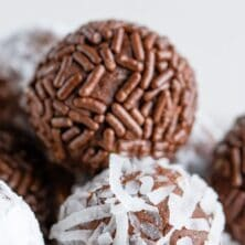Close up shot of chocolate avocado truffles with sprinkles and coconuts on the outside with recipe title on top of image