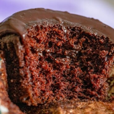 The best chocolate cupcake cut in half to show the fluffy inside with recipe title on top of image