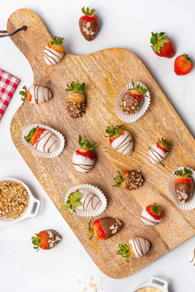 Overhead shot of chocolate covered strawberries with different toppings on a wood cutting board