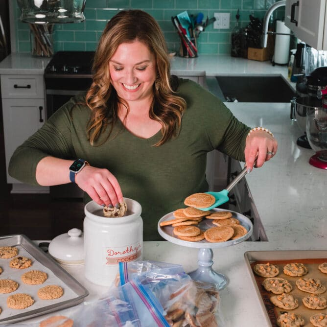woman in green shirt standing at kitchen counter placing cookie in cookie jar with cookies all around on counter