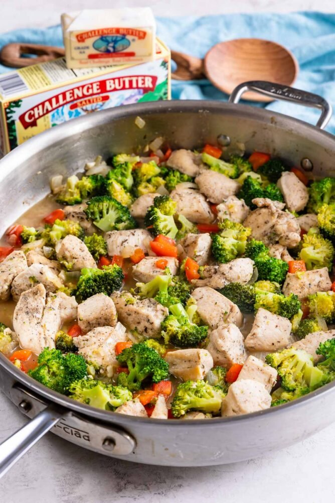 garlic butter chicken and vegetables in skillet with butter behind