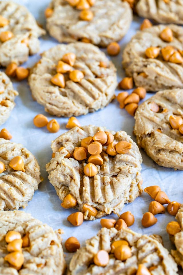 Peanut butter butterscotch cookies on parchment paper with extra butterscotch chips