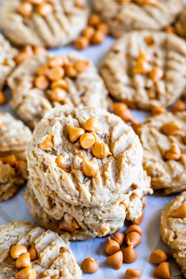 Peanut butter butterscotch cookies stacked on eachother with more surrounding them