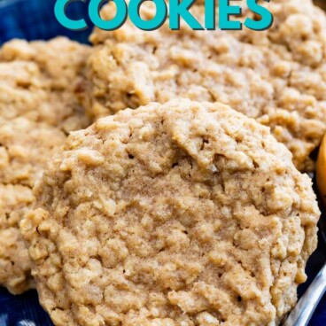 Three peanut butter oatmeal cookies on a royal blue plate next to a spoonful of peanut butter with recipe title on top of image