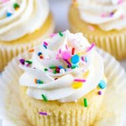 Close up of perfect vanilla cupcake with vanilla buttercream and topped with rainbow sprinkles