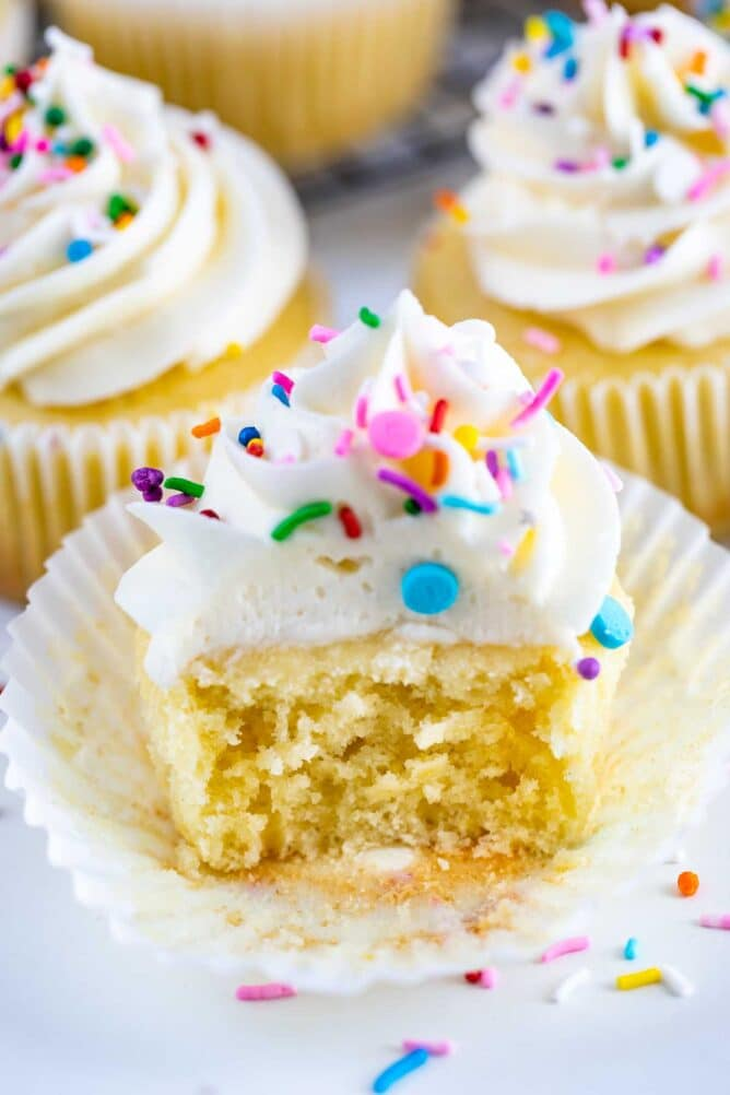 Perfect vanilla cupcake with vanilla buttercream cut in half to show fluffy inside