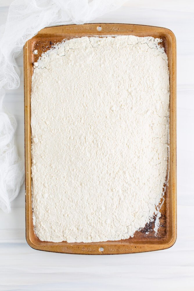 Overhead shot of flour spread out on a baking sheet