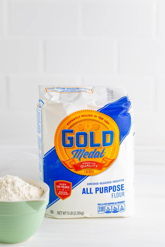 All purpose flour in the bag sitting next to a bowl full of flour