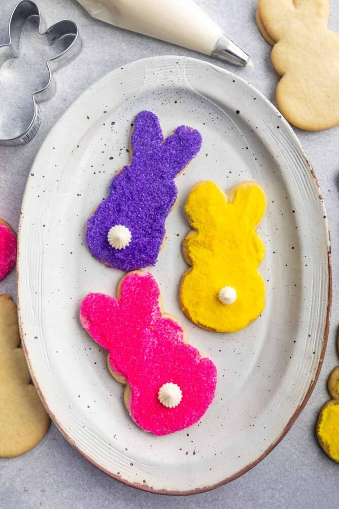 Overhead shot of three decorated bunny cookies on a white serving plate