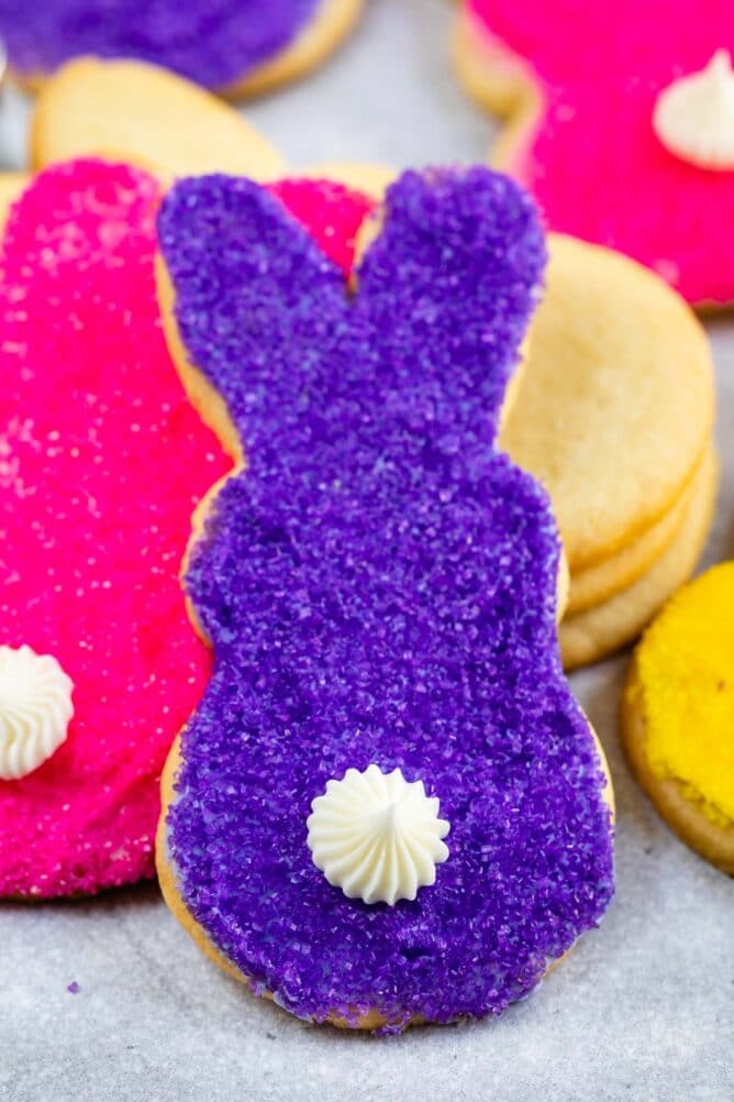 Close up shot of purple and pink bunny butt cookies with white icing tail