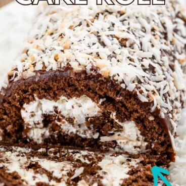Chocolate coconut cake roll on a plate with one slice cut off and shredded coconut all around and recipe title on top of image