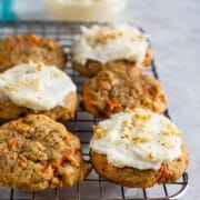 Carrot cake cookies on metal cooling rack, some with frosting on top
