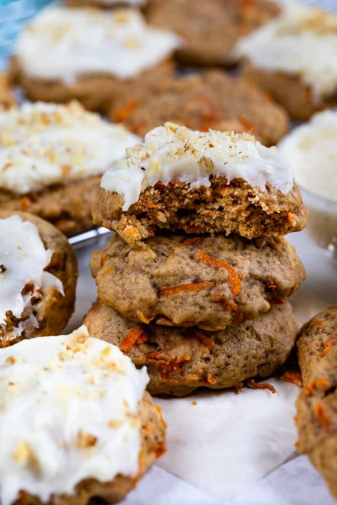 Carrot cake cookies stacked on eachother with top one covered in cream cheese frosting and bite missing