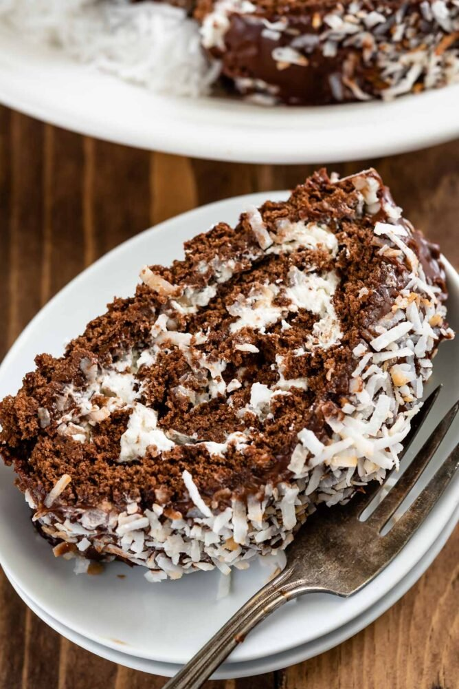 Slice of chocolate coconut cake roll on a white plate with fork