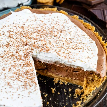 Chocolate cream pie in a glass pie dish with one slice missing