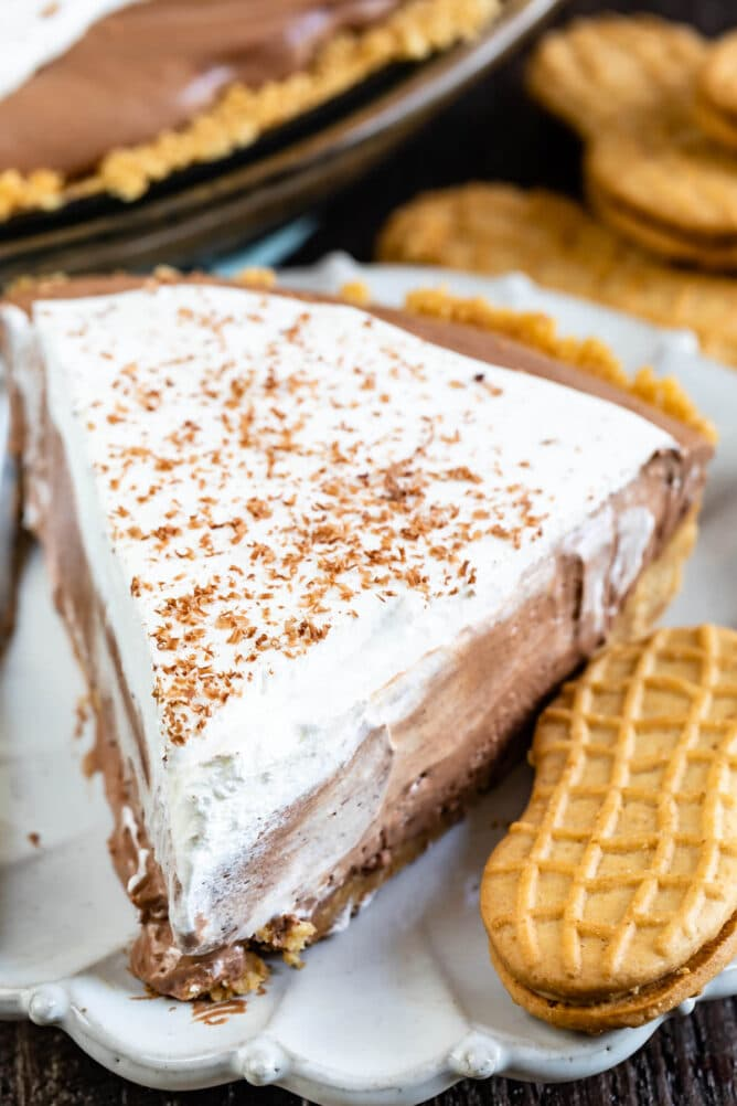 Close up of one slice of chocolate cream pie on a plate next to a peanut butter cookie