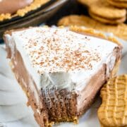 Close up of one slice of chocolate cream pie on a plate with one bite missing