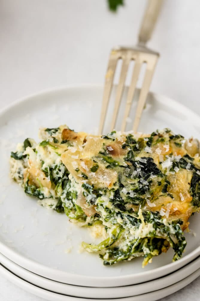 One slice of crustless quiche on a white plate with fork