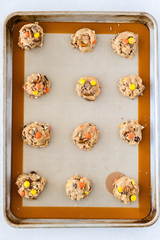 Toffee pretzel peanut butter cookie dough balls on baking sheet