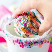 Hand placing one white hot chocolate bomb inside a mug