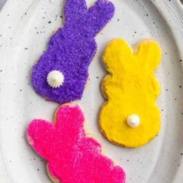 Overhead shot of three decorated bunny cookies on a white serving plate with recipe title on top of image
