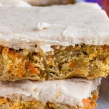 Stack of two carrot cake blondies on parchment paper with recipe title on top of image