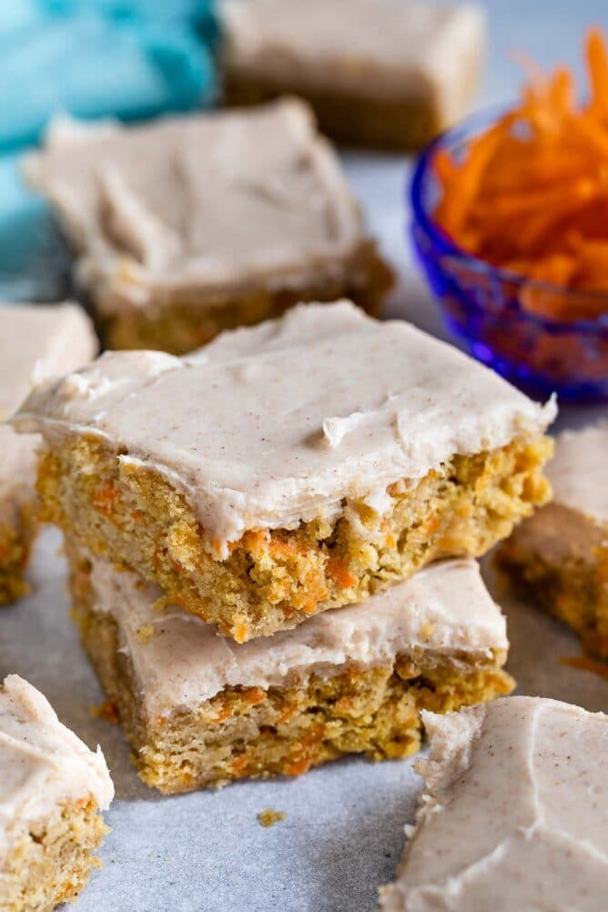 Stack of two carrot cake blondies on parchment paper