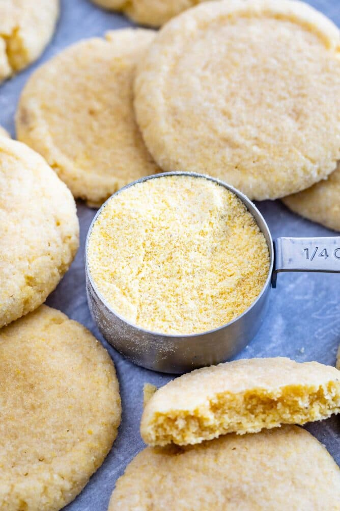 Overhead view of cornmeal cookies with a stainless steel measuring cup full of cornmeal