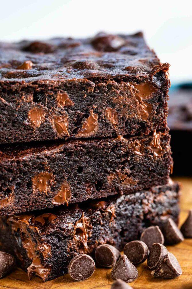 Stack of dark chocolate brownies with chocolate chips around them