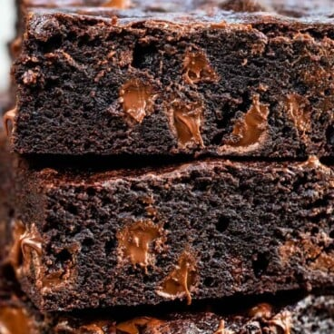 Stack of dark chocolate brownies with chocolate chips around them and recipe title on top of image