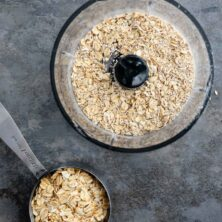 Overhead shot of old fashioned oats in a food processor after being processed and cup of old fashioned oats next to it