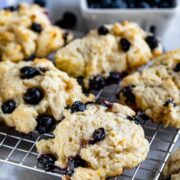 close up of blueberry biscuit on rack with blueberries behind