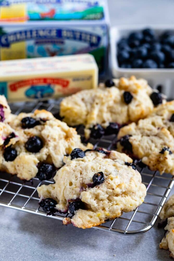close up of blueberry biscuit on rack with blueberries and Challenge butter behind