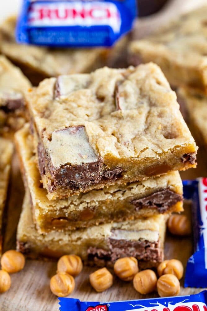 Stack of caramel crunch blondies with crunch candy bars next to it