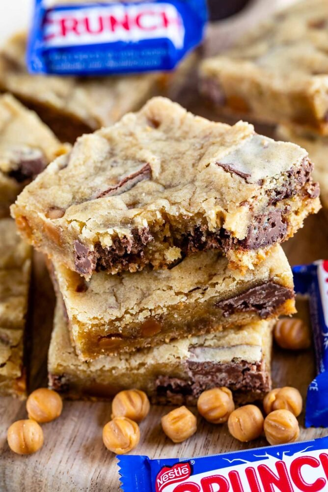 Stack of caramel crunch blondies with top blondie missing a bite and crunch candy bars next to it