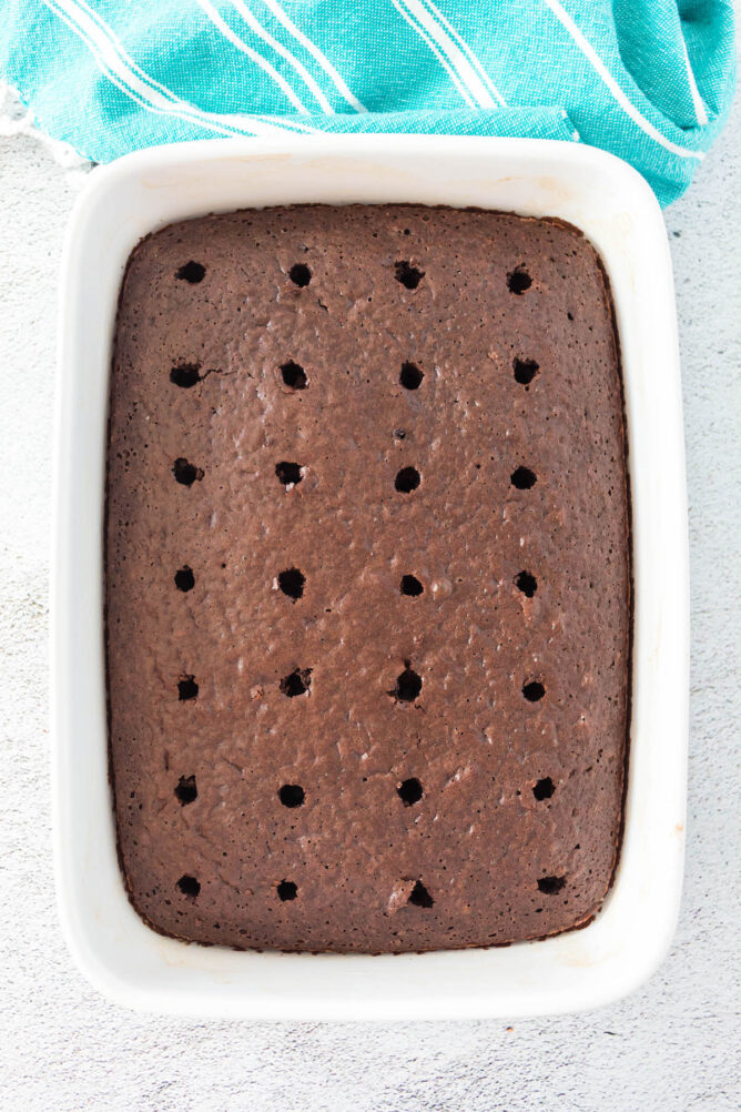 Overhead shot of chocolate poke cake with the holes poked
