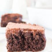 One slice of chocolate poke cake on a white plate