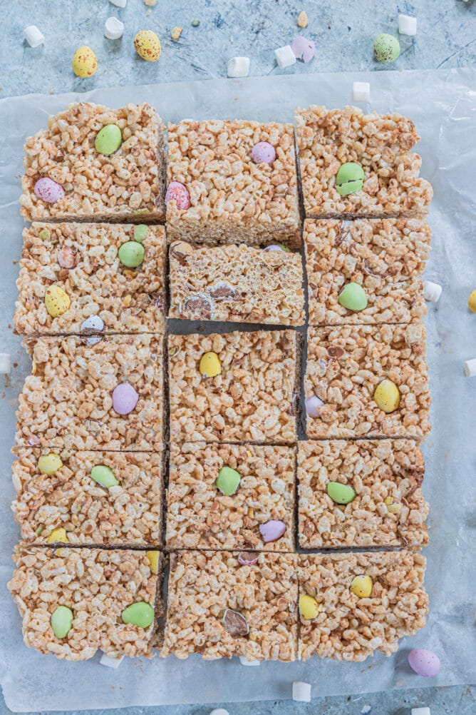 Overhead shot of Easter rice krispie treats cut into squares on parchment paper