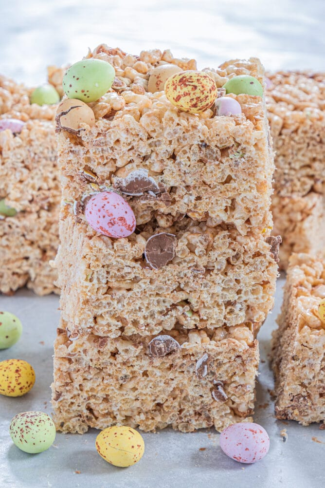 Three Easter rice krispie treats stacked on eachother with more chocolate egg candies around them