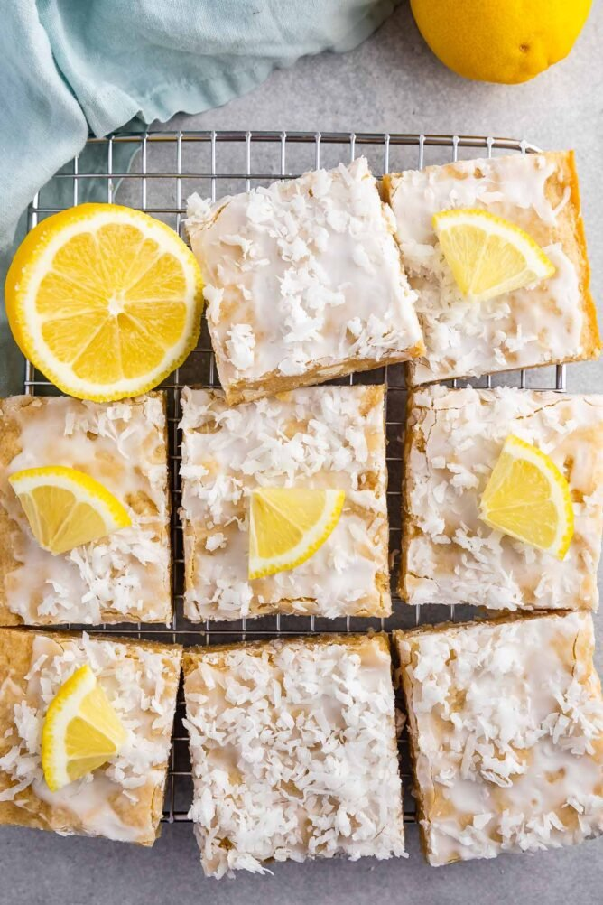 Overhead shot of lemon coconut blondie squares on a wire cooling rack with lemon wedges on top