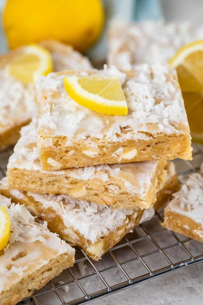 Stack of three lemon coconut blondies with a lemon slice on top
