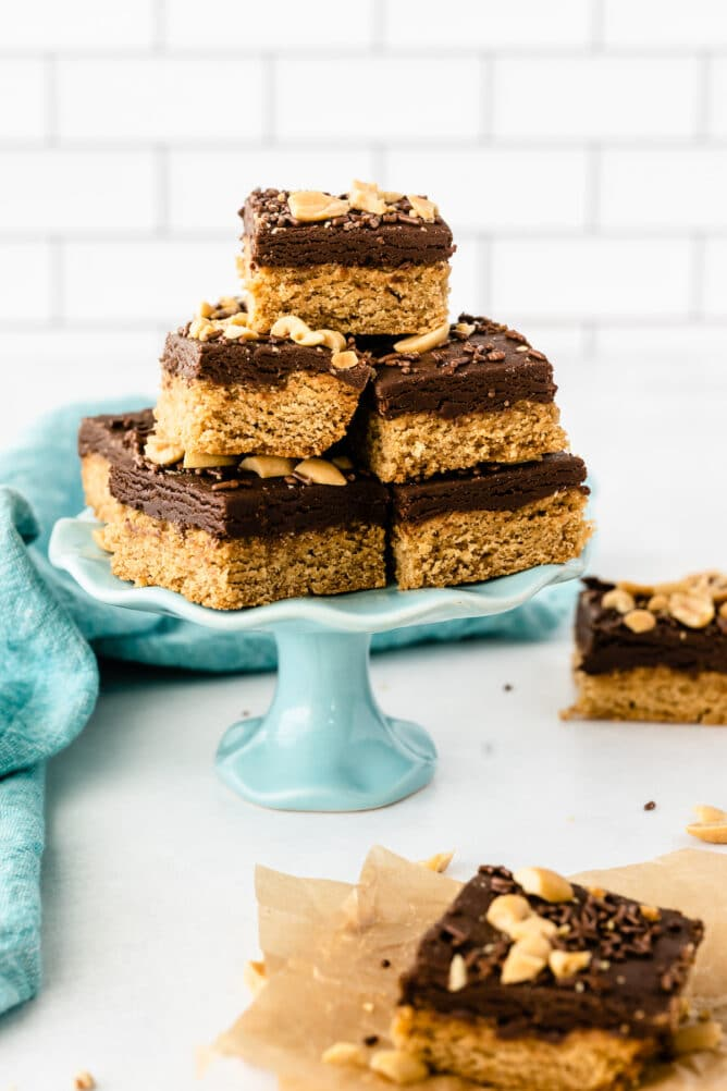 Peanut butter cookie fudge bars cut into squares and placed on a turquoise cake stand