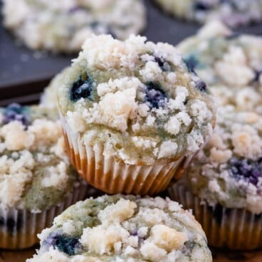 blueberry muffin sitting on stack of muffins