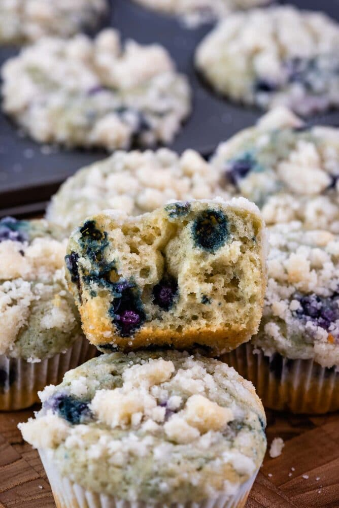 cut in half blueberry muffin sitting on stack of muffins