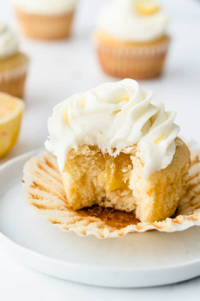 A perfect triple lemon cupcake cut in half to show lemon curd filling