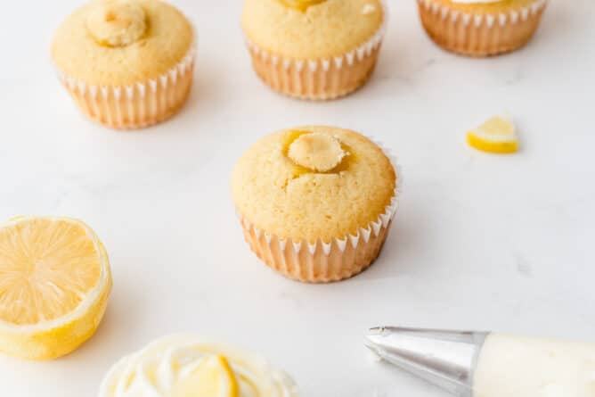 Perfect triple lemon cupcakes with tops put back on after being filled with lemon curd