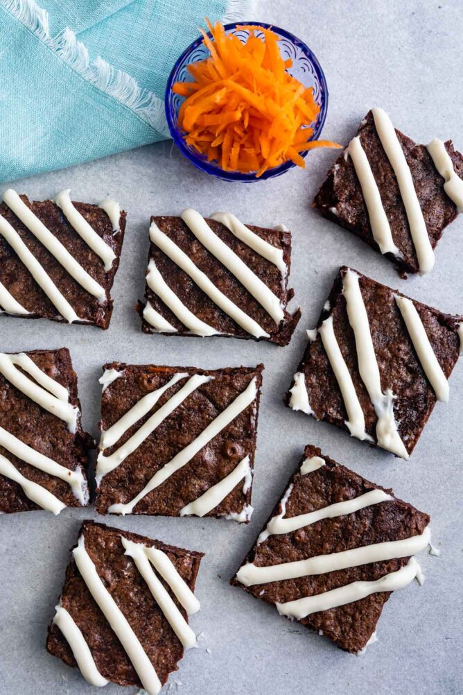 Overhead shot of carrot cake brownies cut into squares next to a cup of shredded carrots