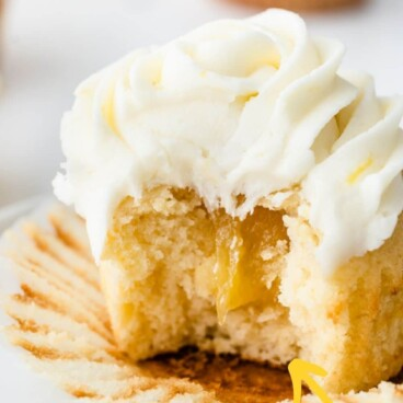 A perfect triple lemon cupcake cut in half to show lemon curd filling with recipe title on top of image